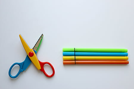 closeup photo of multicolored scissors and pens on white surface