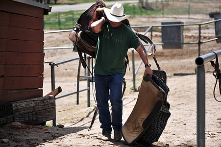 man in green crew-neck shirt holding brown horse saddle