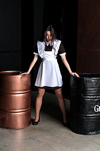 girl wearing black and white maid outfit holding two black and brown metal barrels inside room