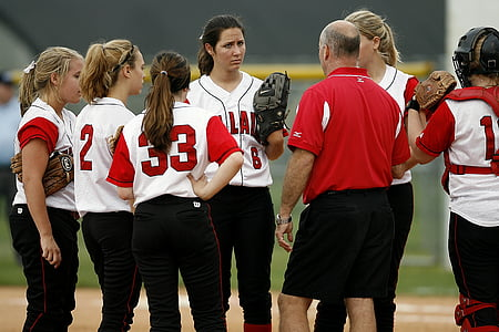 group of women baseball players talking a strategy at daytime
