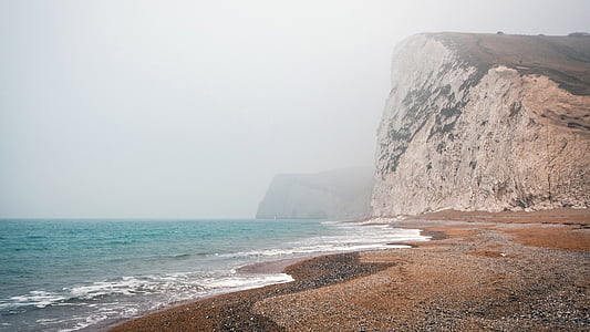 landscape photo of seashore with mountain as background