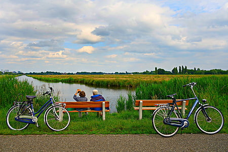 two bicycles on road with two people sitting on bench