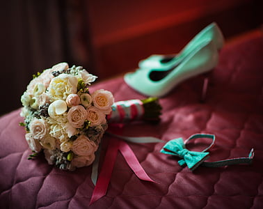 white and pink rose boquet beside teal bow tie and pair or white pumps