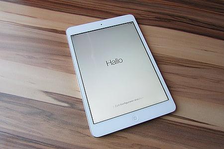 white iPad on brown parquet flooring