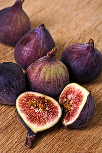 shallow focus photo of purple figs on brown wooden surface