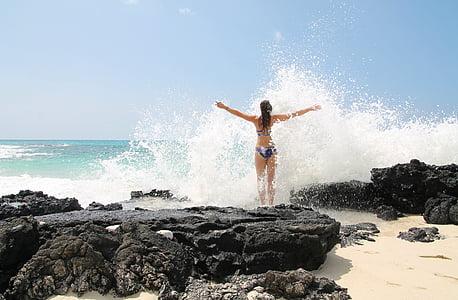 woman in black two piece bikini standing beside body of water
