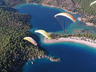 three people riding a parachute