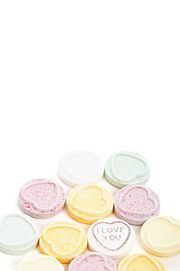 heart-shaped assorted-color candies on white pad