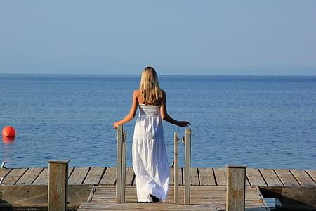 woman wearing white tube dress on brown wooden dock during daytime