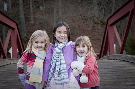 three girls posing for a photo on a bridge