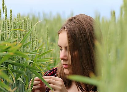 woman holding grain in middle of field