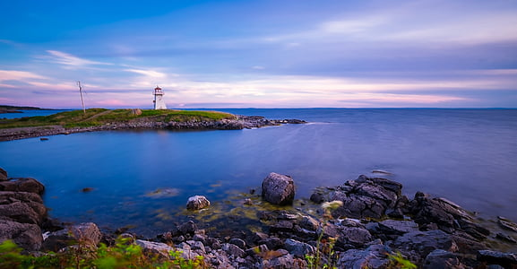white lighthouse beside body of water