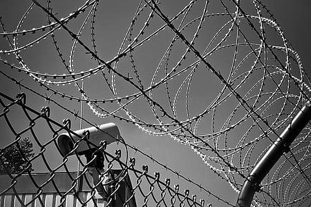 grayscale photo of CCTV camera near bulb wire fence