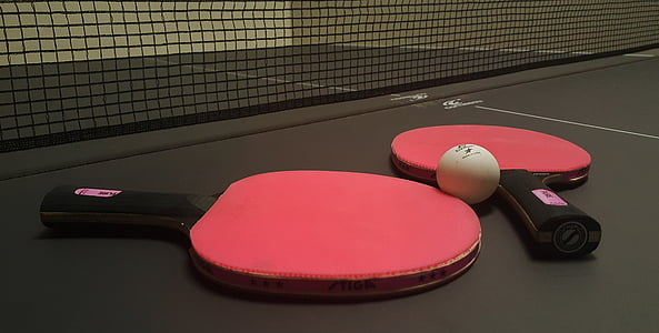 two red ping pong paddles beside of white ball