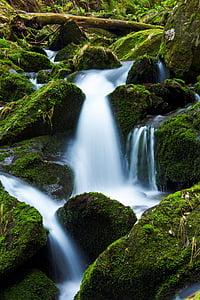 waterfalls on green rocks