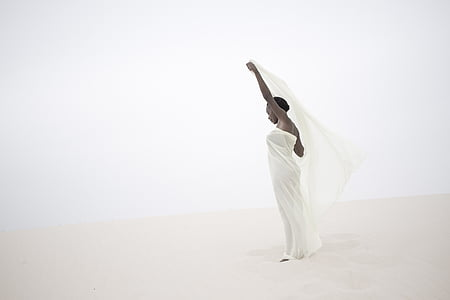 woman wearing white spaghetti strap dress holding white shawl