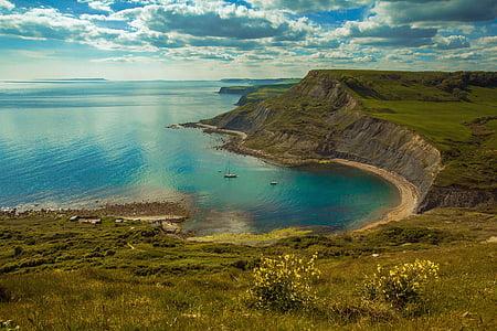 green hill near sea at daytime