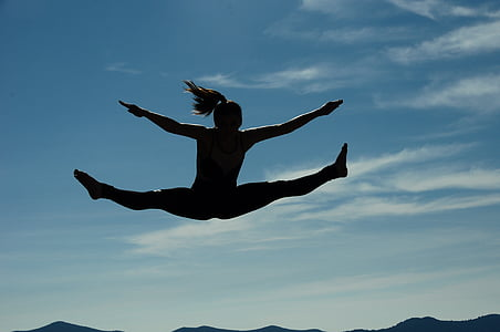 silhouette photography of woman jumping at daytime