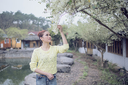 woman wearing green knitted sweater holds white flower at daytime