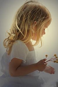 girl in white dress holding flowers