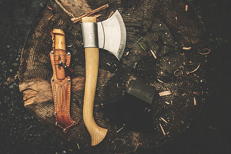 brown and silver hatchet beside brown leather knife sheath on wood stump