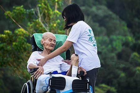 grandfather sitting on wheel chair beside girl