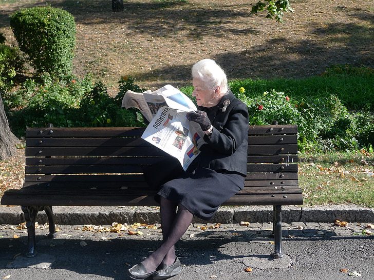 woman sitting on bench reading newspaper at daytime