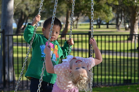 two toddler's riding on swing