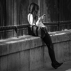 woman using smartphone leaning on wall