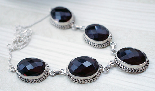 silver-colored black gemstone studded necklace on beige surface