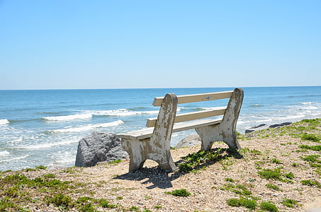 photography of bench on beach shore