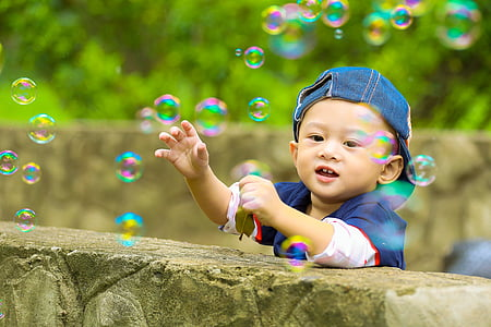 boy standing besides ledge looking at bubbles