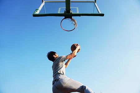 man holding ball near basketball hoop