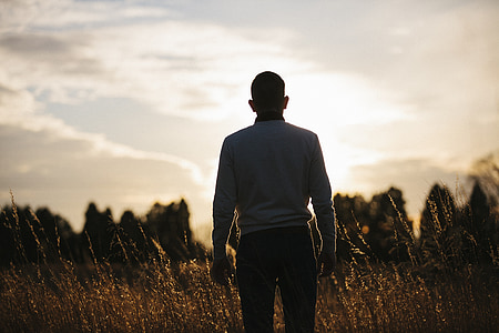 silhouette photo of man standing during golden hour