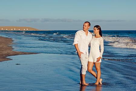 photography of man holding woman on seashore