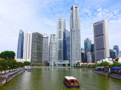 brown and white boat on water near grey high rise buildings under blue and white cloudy sky