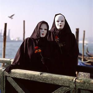 two person wearing black capes and white masks