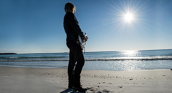 person playing guitar standing on shoreline facing on ocean