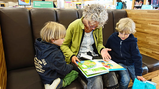 woman with two kids reading book
