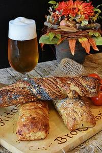 baguette on top of brown board near beer glass