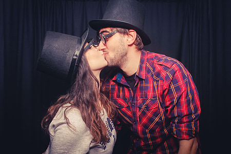 man kissing woman wearing black hats