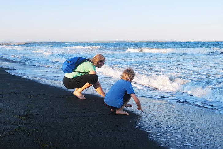 girl and child sitting on seashore