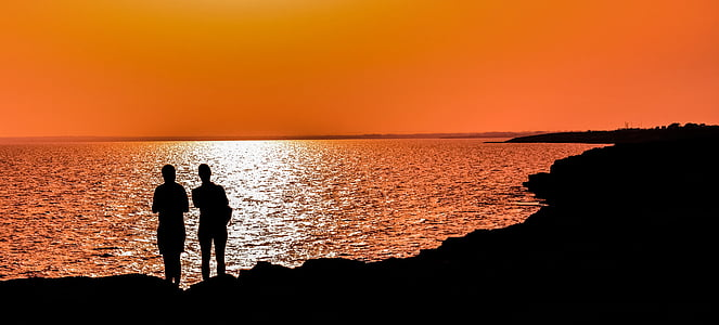 silhouette of two person standing near body of water