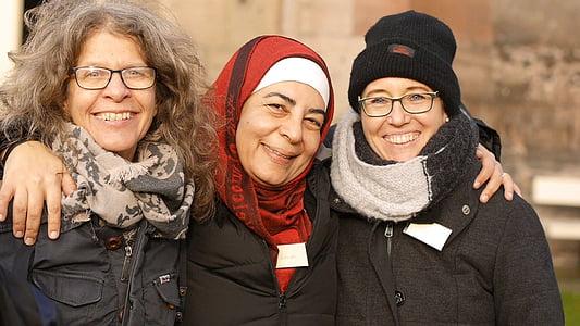 three smiling women in winter tops