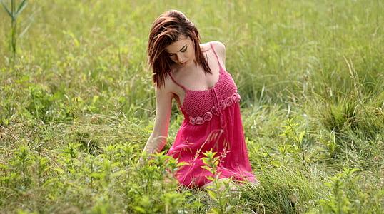 woman wearing red spaghetti strap dress on grass field