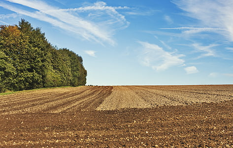 brown soil field under cloudy sky during daytime