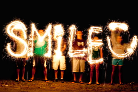 people holding yellow LED light and forming SMILE words