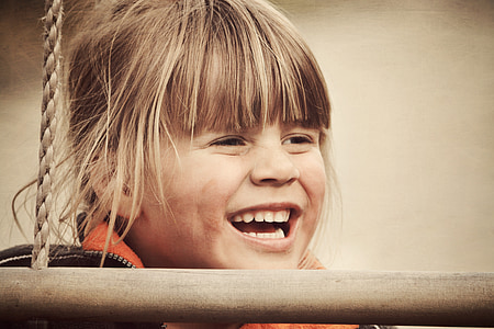 smiling girl behind wood and rope