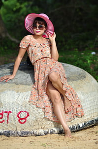 woman in brown floral dress leaning on brown rock posing for photoshoot