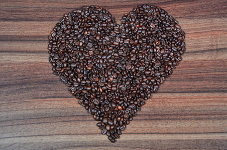 coffee beans in heart formation on brown wooden table